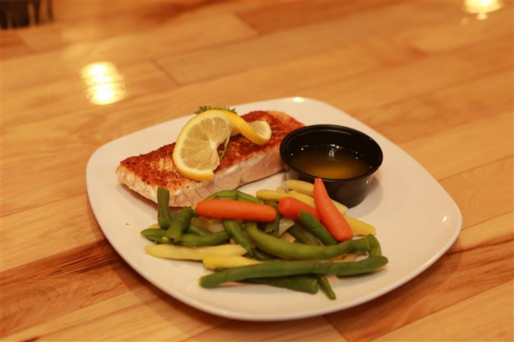 Grilled Salmon with lemon on top and a side of mixed vegetables and butter.