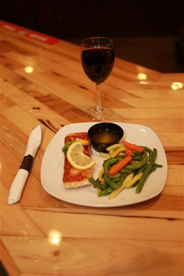 Grilled Salmon with lemon on top and a side of mixed vegetables and butter. Glass of red wine is on the side.