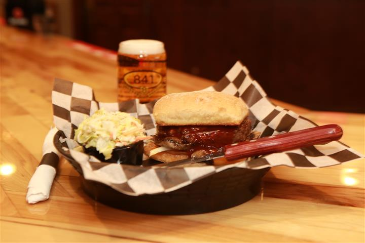 Sandwich with beef and covered in BBQ sauce and a side pickle spear. Light beer on the side.