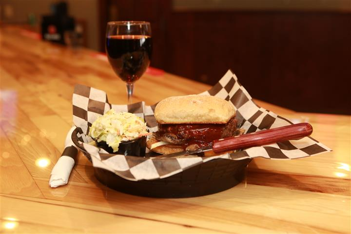 Sandwich with beef and covered in BBQ sauce and a side pickle spear. Red wine on the side.
