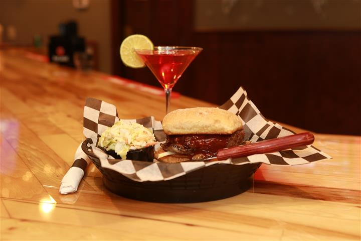 Sandwich with beef and covered in BBQ sauce and a side pickle spear. Red martini with lime slice on the side.