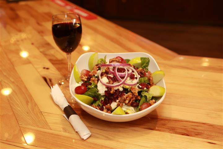 Apple Walnut Salad with red wine on the side on a wooden table.