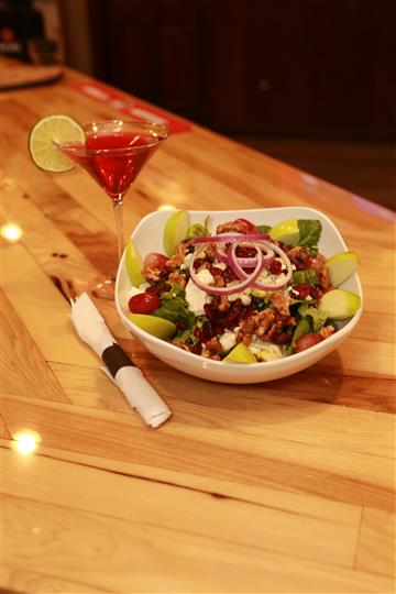 Apple Walnut Salad with red martini with a lime slice on the side on a wooden table.