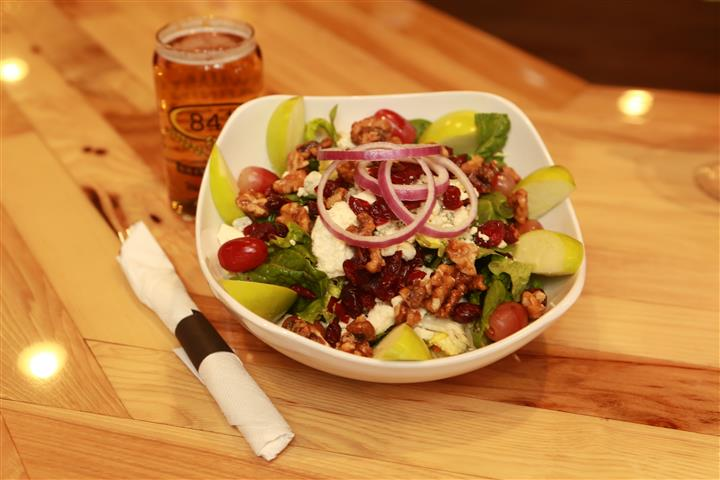 Apple Walnut Salad with light beer on the side on a wooden table.