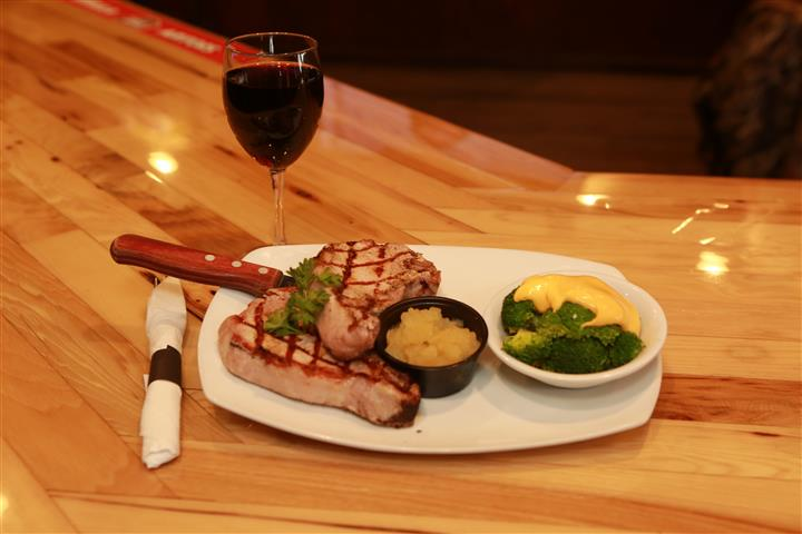 Steak with a side of broccoli on a white plate with a glass of red wine on a wooden table.