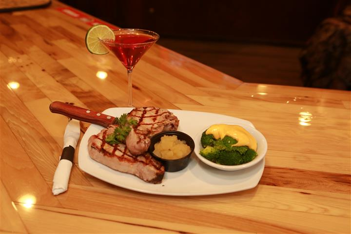 Steak with a side of broccoli on a white plate with a red martini with a lime slice on a wooden table.