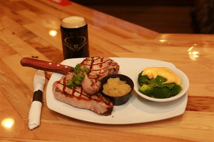 Steak with a side of broccoli on a white plate with a dark beer on a wooden table.