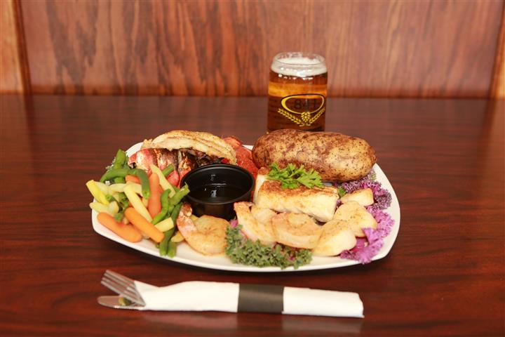 Entree with a baked potato and beer battered shrimp on the side. Served with a light beer.