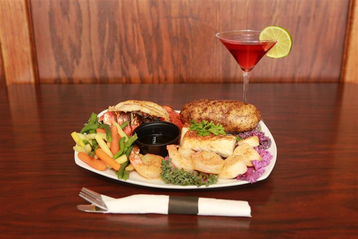 Entree with a baked potato and beer battered shrimp on the side. Served with a red martini with a lime slice.