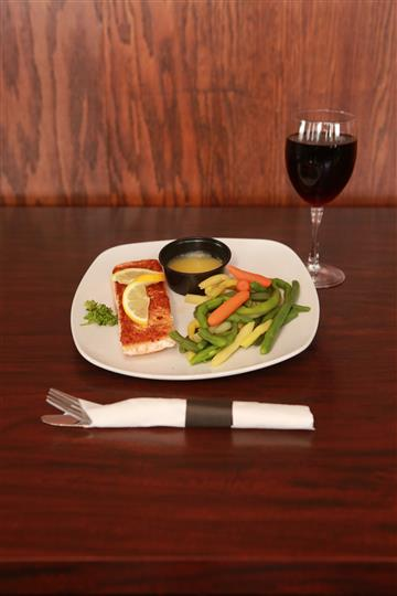 Seafood entree served with a side of butter and a vegetable mix. Also served with a glass of red wine on the side.
