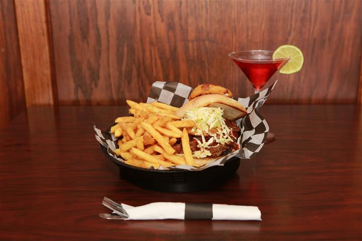 Brew House Specialty Sandwich topped with coleslaw with a side of french fries. Served with a red martini with a lime slice.