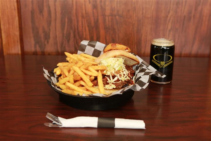 Brew House Specialty Sandwich topped with coleslaw with a side of french fries. Served with a dark beer.
