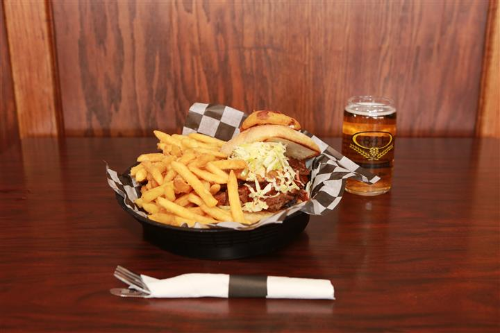 Brew House Specialty Sandwich topped with coleslaw with a side of french fries. Served with a red martini with a light beer.