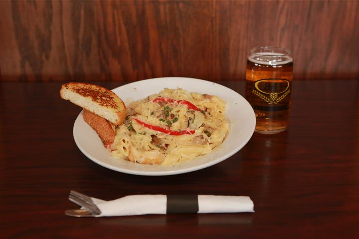 LaBella pasta with two pieces of bread and a light beer.