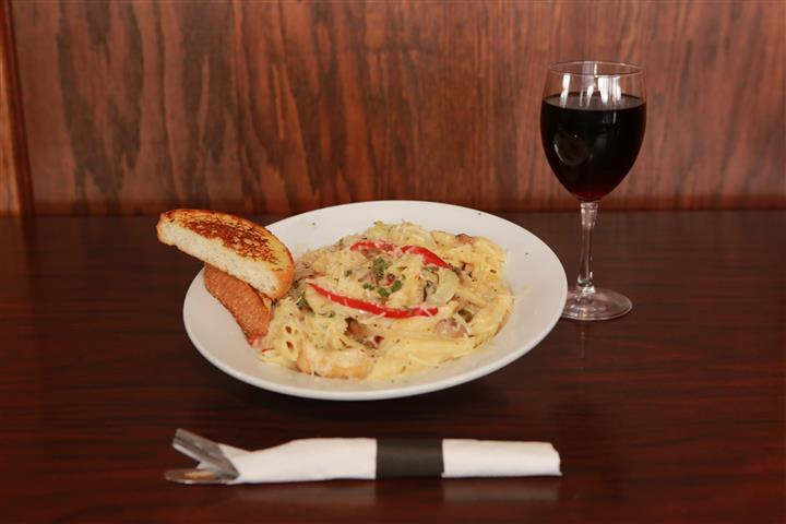 LaBella pasta with two pieces of bread and a glass of red wine.
