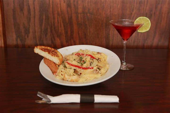 LaBella pasta with two pieces of bread and a red martini with a lime slice.