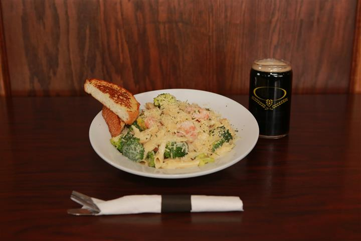 Pasta dish with a light cream sauce, mixed with broccoli and shrimp. Served with dark beer.