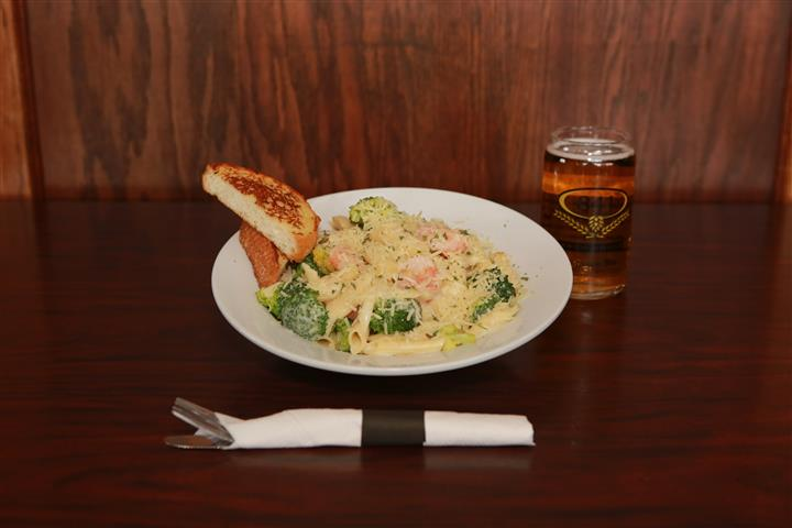 Pasta dish with a light cream sauce, mixed with broccoli and shrimp. Served with light beer.