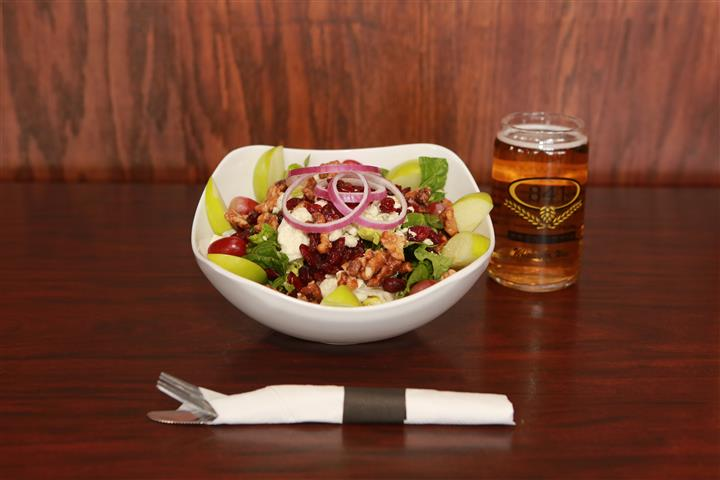 Apple Walnut Salad with a light beer on a wooden table.