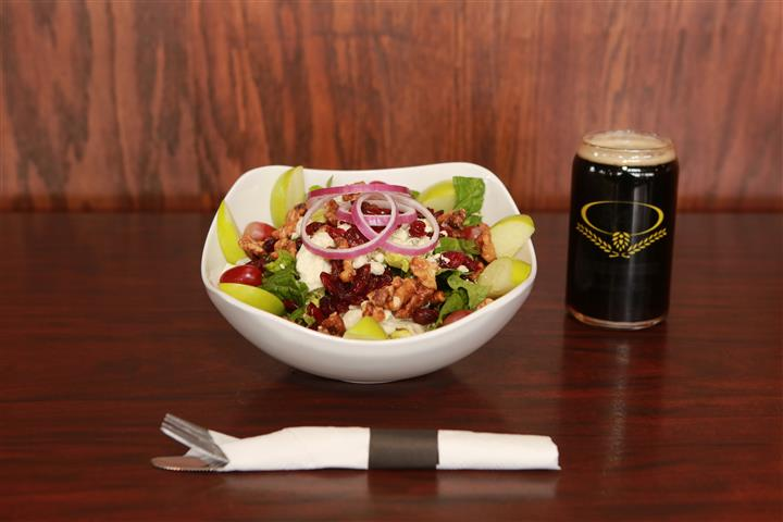 Apple Walnut Salad with a dark beer on a wooden table.