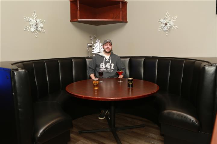 Man sitting in corner round booth with two beers, a glass of red wine and a red martini.