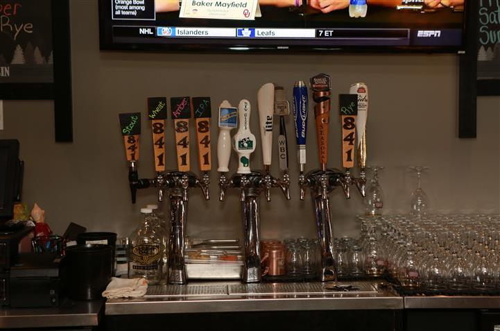 Beer tap behind bar with 12 beer options.
