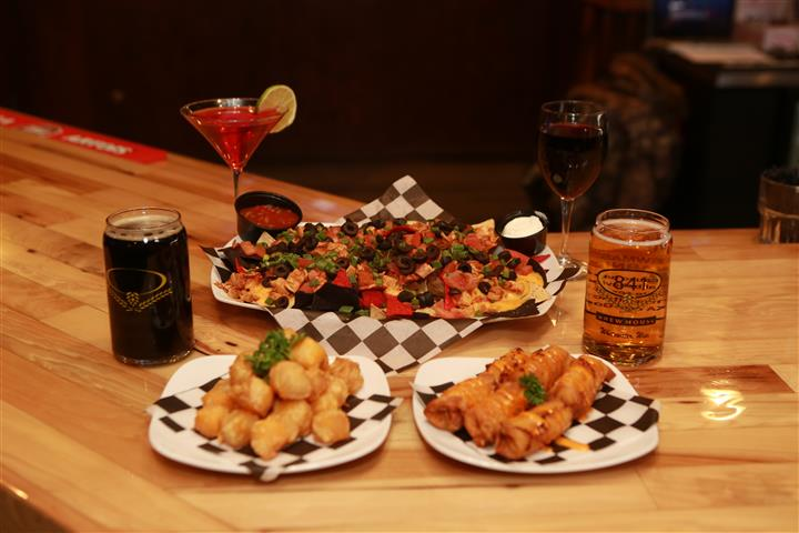 Colby cheese curds, Tatchos, and Bavarian Pretzel Sticks with a glass of red wine, a red martini with a lime slice, a dark beer and a light beer.