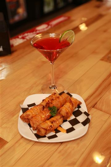 Bavarian Pretzel Sticks with a red martini with a lime slice.