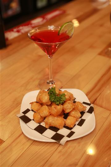 Colby Cheese Curds with a red martini with a lime slice.