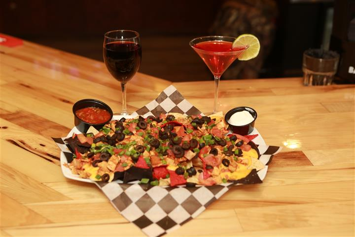 Tatchos with a glass of red wine and a red martini with a lime slice.