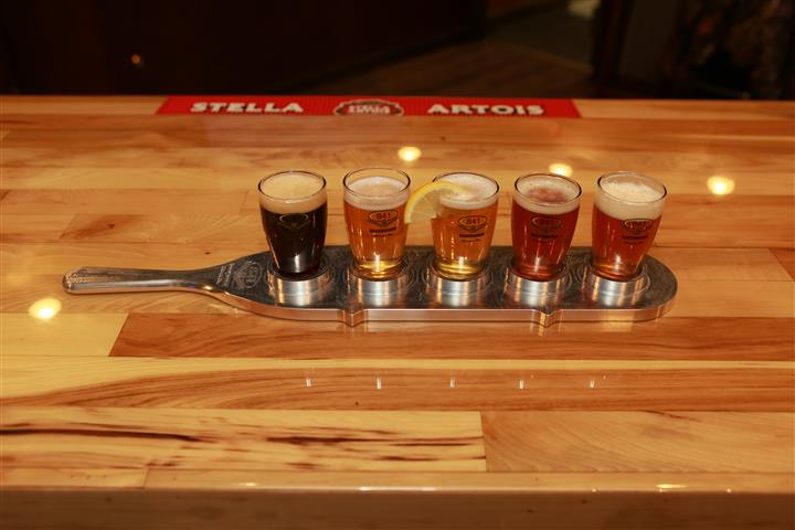 Top view of a flight of 5 beers on a wooden bar top