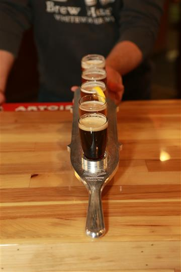 Front view of a flight of 5 beers on a wooden bar top