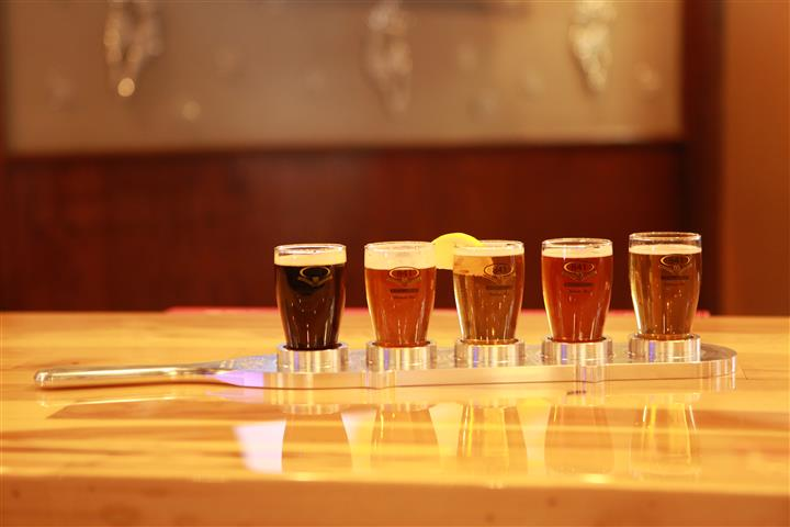 Side view of a flight of 5 beers on a wooden bar top