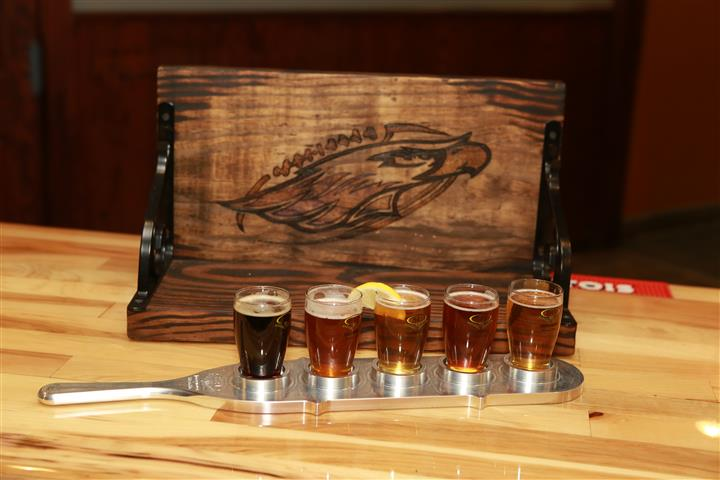 Flight of 5 beers in front of a wooden shelf with an eagle painted on it.