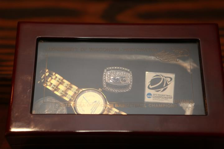 Top view of University of Wisconsin Basketball Champions  memorabilia box with a watch and ring inside.
