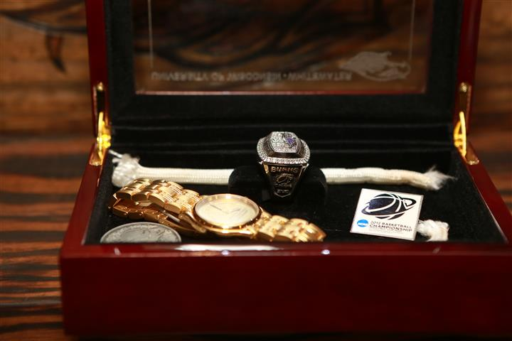 Side view of University of Wisconsin Basketball Champions  memorabilia box with a watch and ring inside.