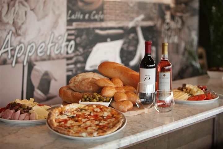 an assortment of pizza, bread and wine bottles on a counter