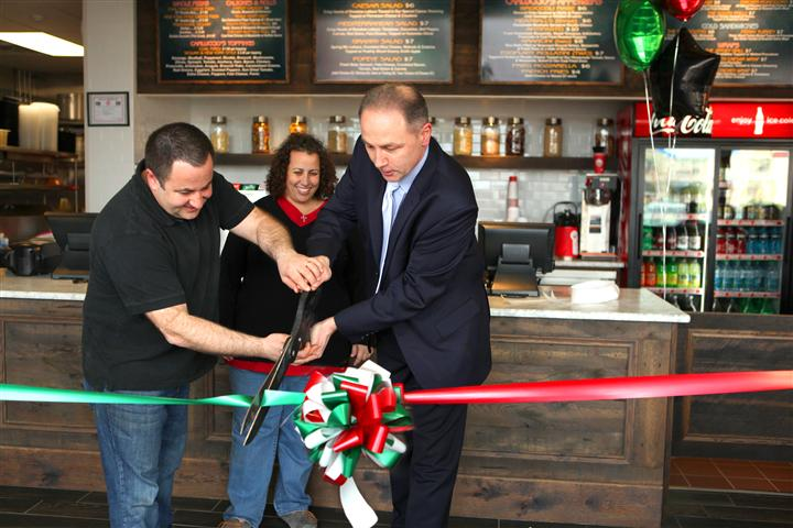 owners and chef cutting ribbon inside during opening day