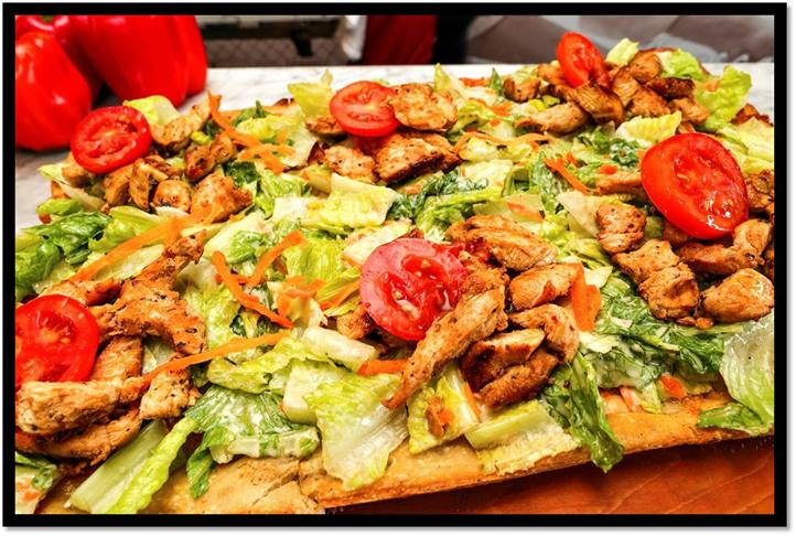 large wooden board topped with salad, chicken slices and tomatoes