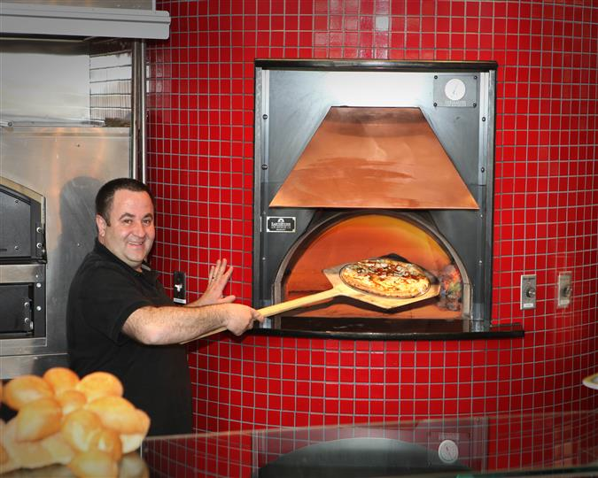 chef smiling at the camera as he places a pizza into the oven