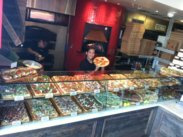 waitress behind a counter of various pizzas on display