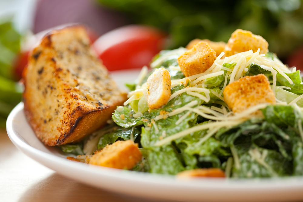 caesar salad with cheese and croutons and garlic bread