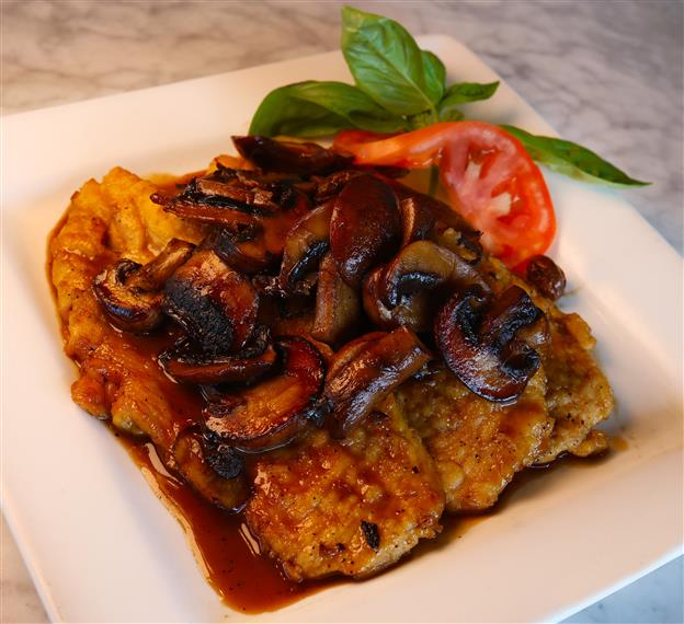 chicken marsala with mushrooms on top and a tomato on the side