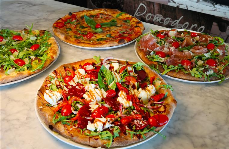 4 different specialty pizza pies on a table