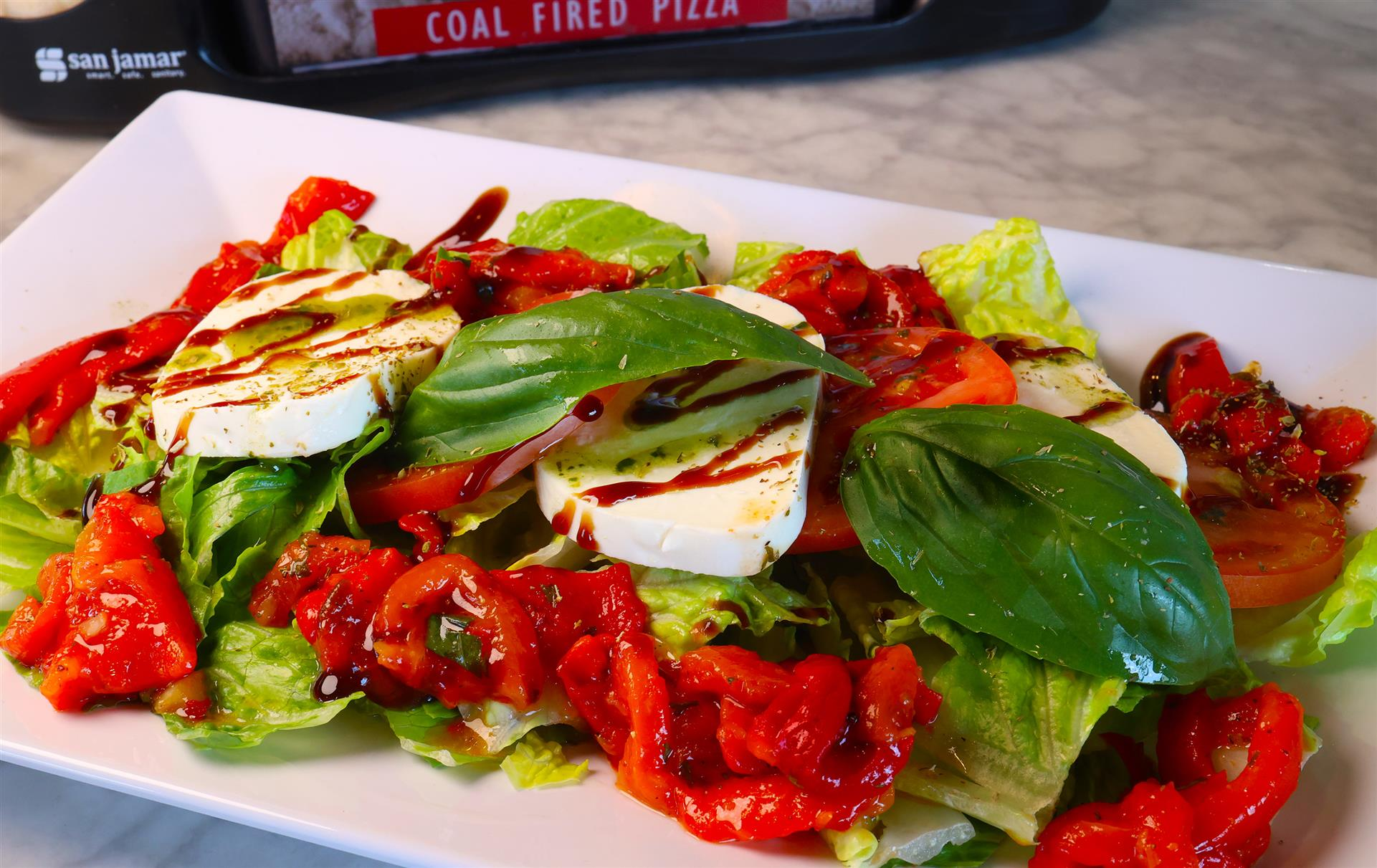 iceberg lettuce with roasted red peppers, sliced mozzarella and tomatoes with a balsamic drizzle