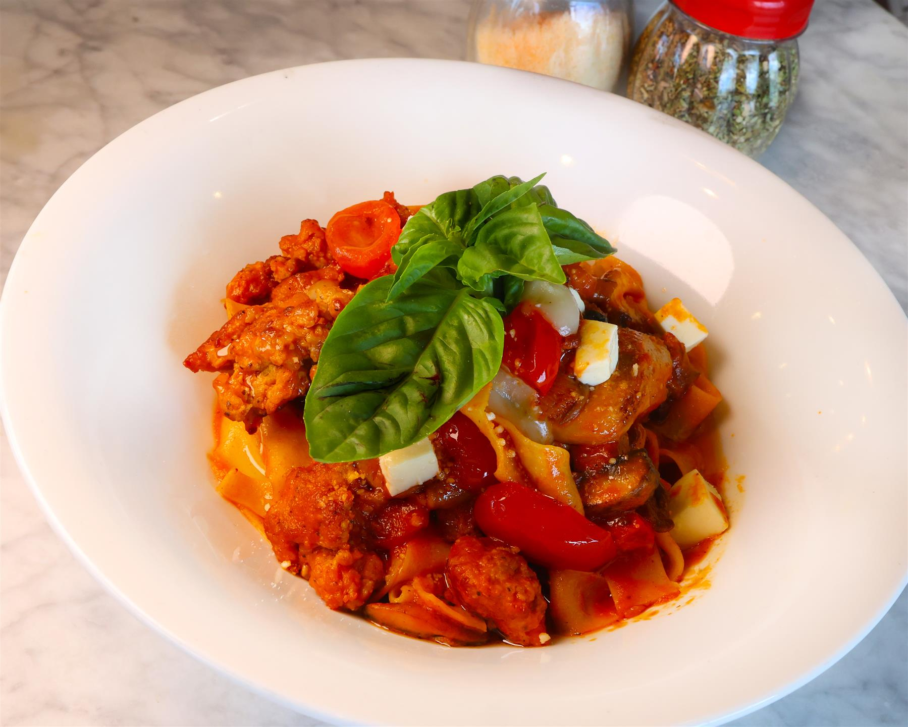 Pappardelle Alla Siciliana with Fresh Pappardelle Pasta with Cherry Tomatoes, Assorted Mushrooms, Eggplant and Italian Sausage topped with Homemade Melted Mozzarella