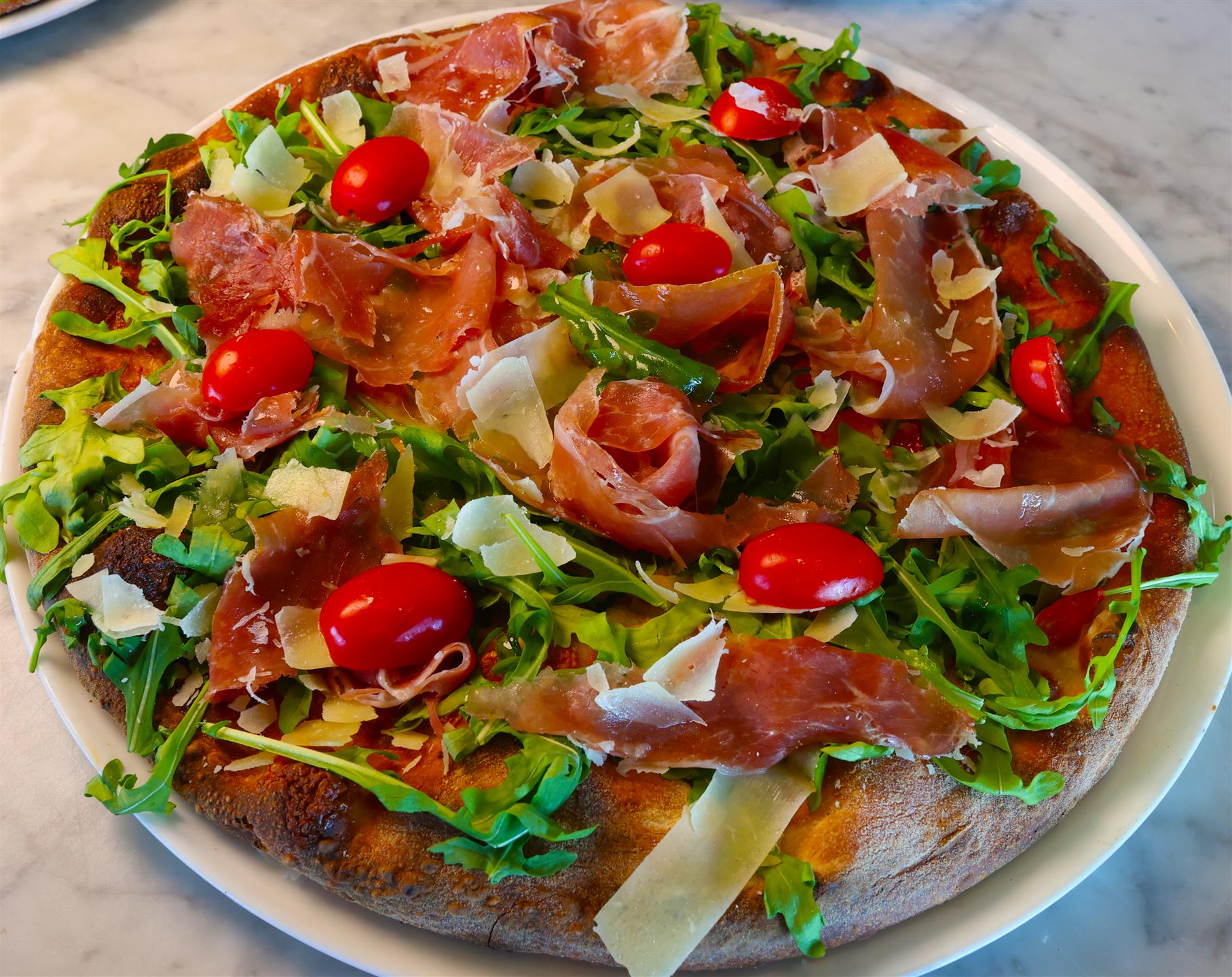 pizza with arugula, tomatoes, shaved cheese, and prosciutto