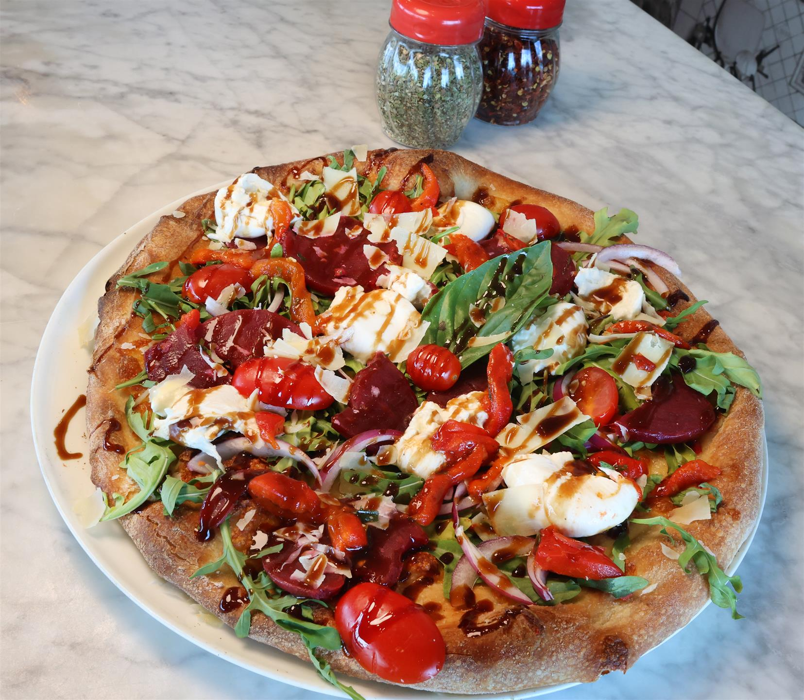 pizza with arugula, tomatoes, mozzarella, beets, and a balsamic drizzle