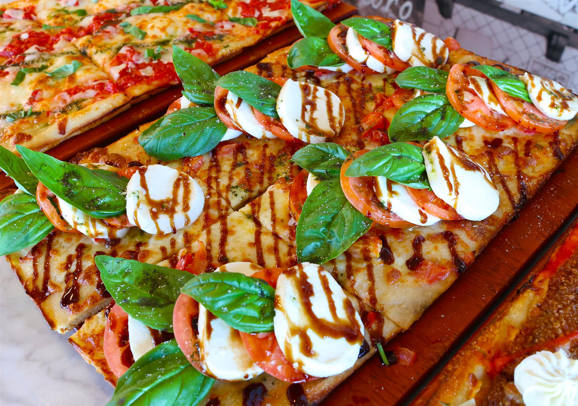 flatbread with sliced mozzarella, tomatoes, basil and a balsamic drizzle