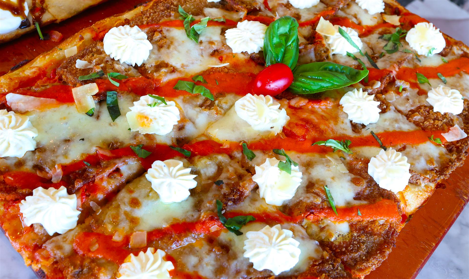 sicilian pizza with dollops of cheese on top and a vodka sauce drizzle